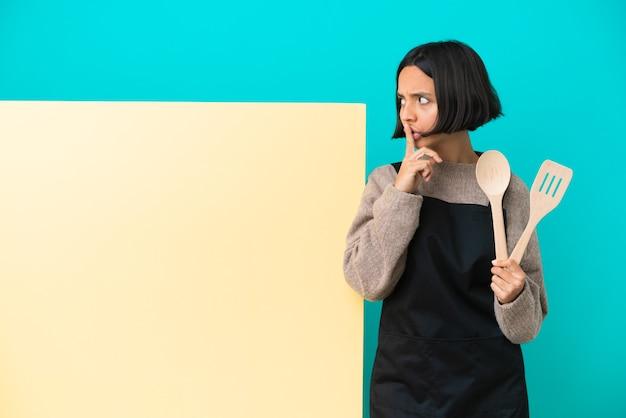 Junge gemischte köchin mit einem großen plakat isoliert auf blauem hintergrund, das ein zeichen der stille zeigt, geste, die den finger in den mund steckt