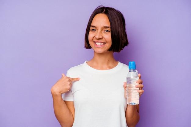 Junge gemischte rasse, die eine wasserflasche einzeln auf violettem hintergrund hält, die mit der hand auf einen hemdkopierraum zeigt, stolz und selbstbewusst