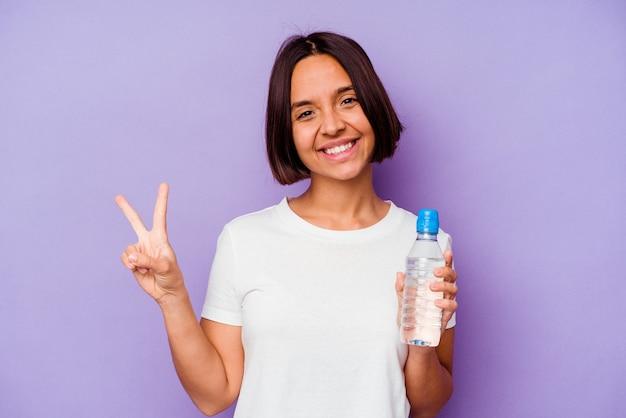 Junge gemischte rasse, die eine wasserflasche isoliert auf violettem hintergrund hält, fröhlich und sorglos, die ein friedenssymbol mit den fingern zeigt.