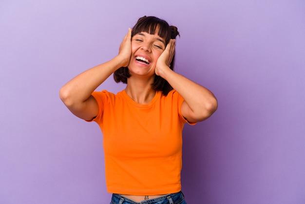 Junge gemischte rasse frau isoliert auf lila hintergrund lacht freudig die hände auf dem kopf halten. glück-konzept.