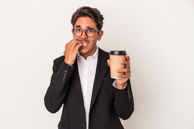 Junge gemischte rasse geschäftsmann hält kaffee zum mitnehmen isoliert auf weißem hintergrund beißende fingernägel, nervös und sehr ängstlich.