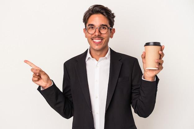Junge gemischte rasse geschäftsmann hält kaffee zum mitnehmen isoliert auf weißem hintergrund lächelnd und beiseite zeigend, etwas an der leerstelle zeigend.