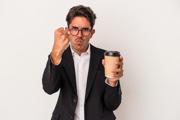 Junge gemischte rasse geschäftsmann hält kaffee zum mitnehmen isoliert auf weißem hintergrund zeigt faust zur kamera, aggressiven gesichtsausdruck.
