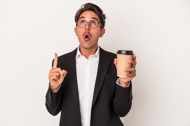 Junge gemischte rasse geschäftsmann hält kaffee zum mitnehmen isoliert auf weißem hintergrund zeigt nach oben mit geöffnetem mund.