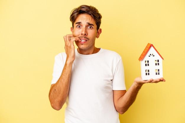 Junge gemischte rasse mann hält spielzeughaus isoliert auf gelbem hintergrund beißende fingernägel, nervös und sehr ängstlich.