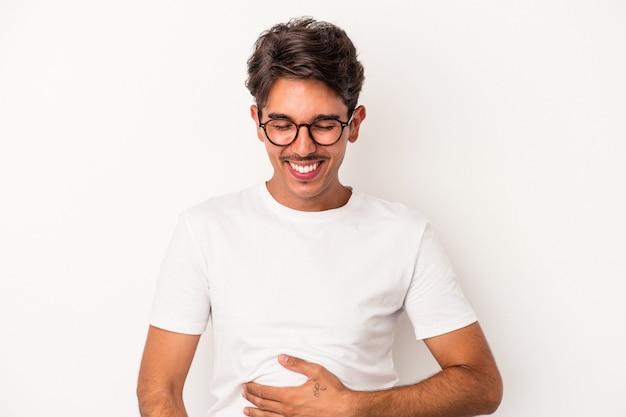 Junge gemischte rasse mann isoliert auf weißem hintergrund berührt bauch, lächelt sanft, essen und zufriedenheit konzept.