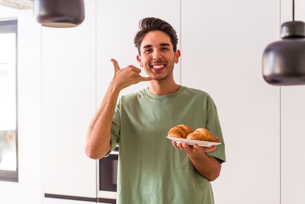 Junge gemischte rasse mann isst croissant in einer küche am morgen und zeigt eine handy-anruf-geste mit den fingern.
