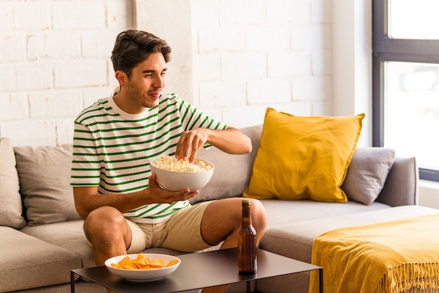 Junge gemischte rasse mann isst popcorn auf dem sofa sitzend