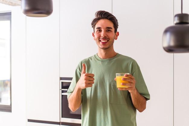Junge gemischte rasse mann trinkt orangensaft in seiner küche lächelnd und daumen hoch