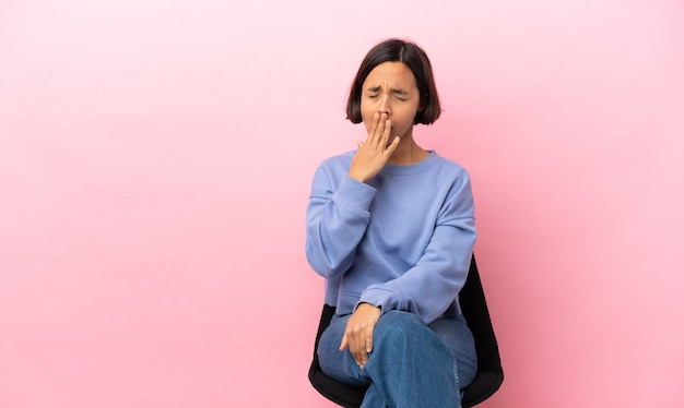 Junge gemischte rassenfrau, die auf einem stuhl lokalisiert auf rosa hintergrund gähnt gähnt und weit geöffneten mund mit hand bedeckt