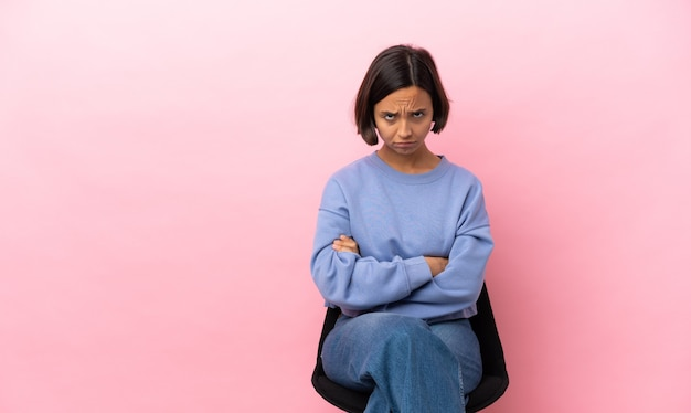 Junge gemischte rassenfrau, die auf einem stuhl lokalisiert auf rosa hintergrund mit traurigem ausdruck sitzt