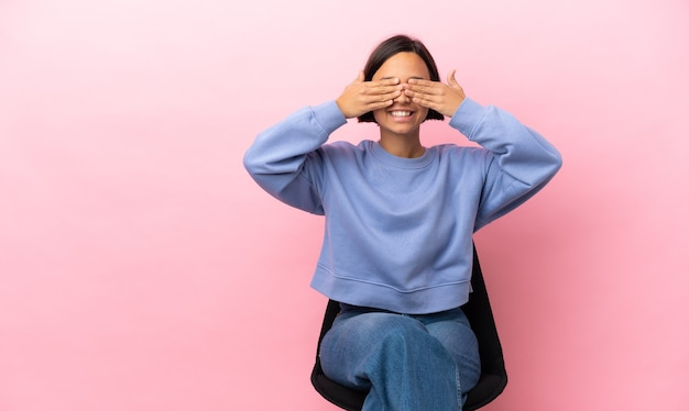 Junge gemischte rassenfrau, die auf einem stuhl lokalisiert auf rosa hintergrund sitzt, der augen durch hände bedeckt und lächelt