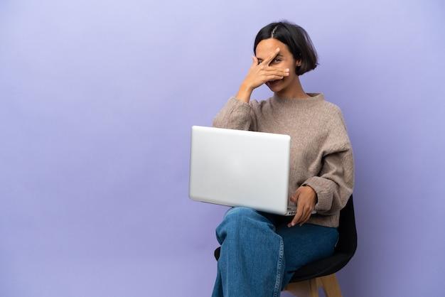 Junge gemischte rassenfrau, die auf einem stuhl mit laptop lokalisiert auf lila hintergrund sitzt, der augen durch hände bedeckt und lächelt