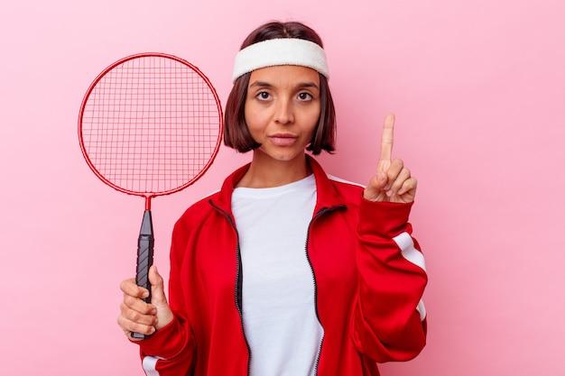 Junge gemischte rassenfrau, die badminton spielt, lokalisiert auf rosa wand, die nummer eins mit finger zeigt.