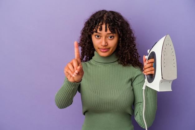 Junge gemischte rassenfrau, die ein eisen lokalisiert auf lila wand zeigt, die nummer eins mit finger zeigt.