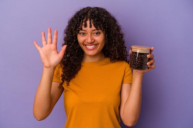 Junge gemischte rassenfrau, die eine kaffeebohnenflasche lokalisiert auf lila wandlächeln fröhlich zeigt nummer fünf mit den fingern hält.