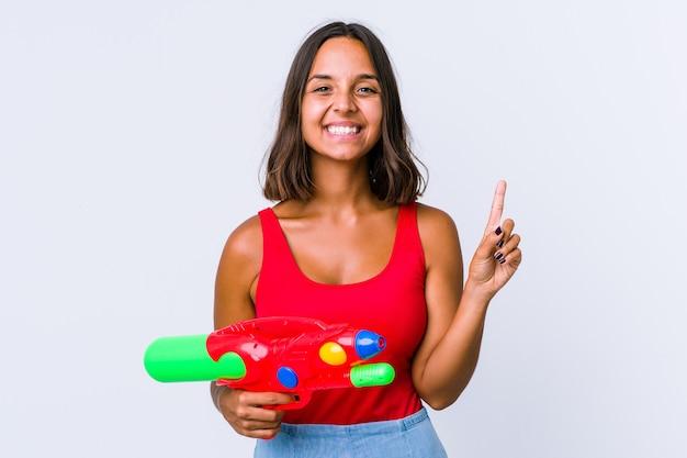 Junge gemischte rassenfrau, die eine wasserpistole isoliert hält, die nummer eins mit finger zeigt.
