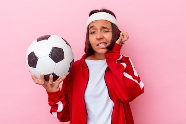 Junge gemischte rassenfrau, die fußball lokalisiert auf rosa hintergrund abdeckt ohren mit händen spielt.