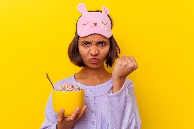 Junge gemischte rassenfrau, die müsli isst, die einen pijama tragen, der auf gelbem hintergrund lokalisiert wird, der faust zur kamera, aggressiven gesichtsausdruck zeigt.