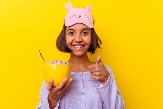 Junge gemischte rassenfrau, die müsli isst, die einen pijama tragen, der auf gelbem hintergrund lokalisiert wird, der lächelt und daumen aufhebt