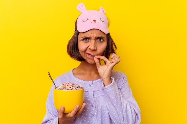 Junge gemischte rassenfrau, die müsli isst, die einen pijama tragen, der auf gelbem hintergrund mit den fingern auf den lippen lokalisiert wird, die ein geheimnis halten.