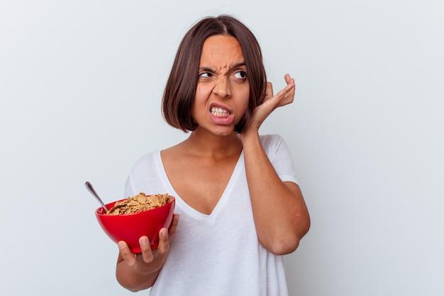 Junge gemischte rassenfrau, die müsli lokalisiert auf weißer wand, die ohren mit händen bedeckt, isst.