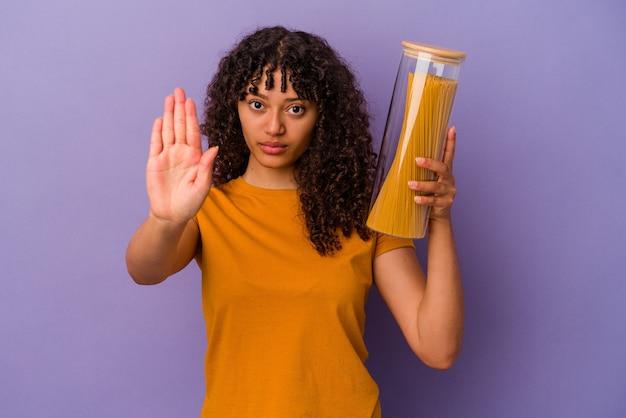Junge gemischte rassenfrau, die spaghetti lokalisiert auf lila wand steht, die mit ausgestreckter hand steht, die stoppschild zeigt, das sie verhindert.