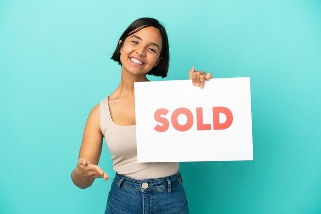 Junge gemischte rassenfrau lokalisiert auf blauem hintergrund, der ein plakat mit dem verkauften text hält, der einen deal macht