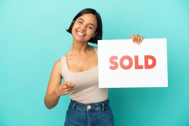 Junge gemischte rassenfrau lokalisiert auf blauem hintergrund, der ein plakat mit text verkauft hält und nach vorne zeigt
