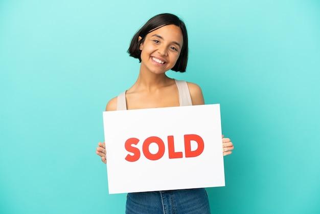 Junge gemischte rassenfrau lokalisiert auf blauem hintergrund, der ein plakat mit text verkauft mit glücklichem ausdruck hält