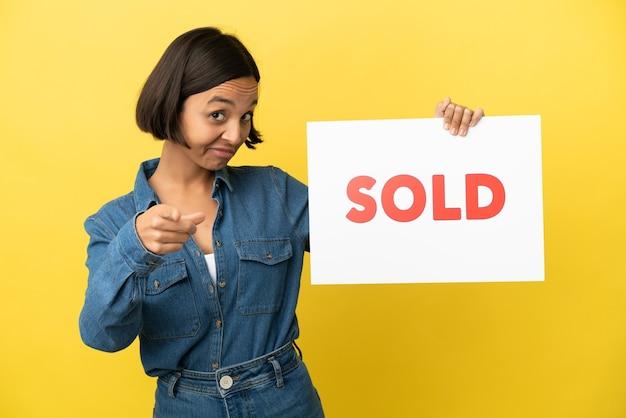 Junge gemischte rassenfrau lokalisiert auf gelbem hintergrund, der ein plakat mit dem text verkauft hält und nach vorne zeigt