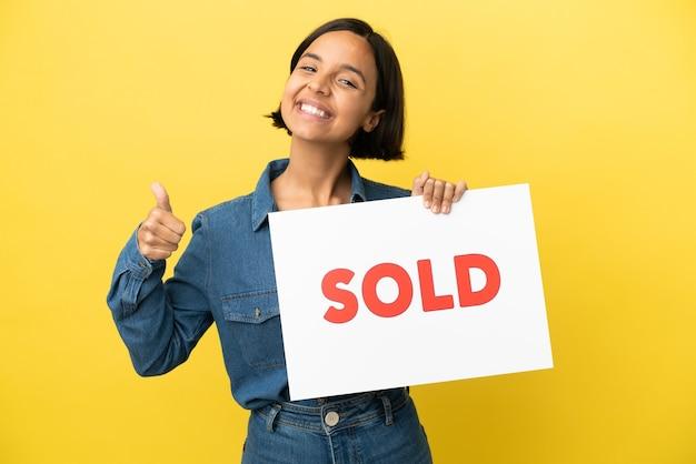 Junge gemischte rassenfrau lokalisiert auf gelbem hintergrund, der ein plakat mit text verkauft mit daumen nach oben hält