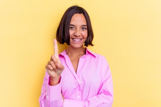 Junge gemischte rassenfrau lokalisiert auf gelbem hintergrund, der nummer eins mit finger zeigt.