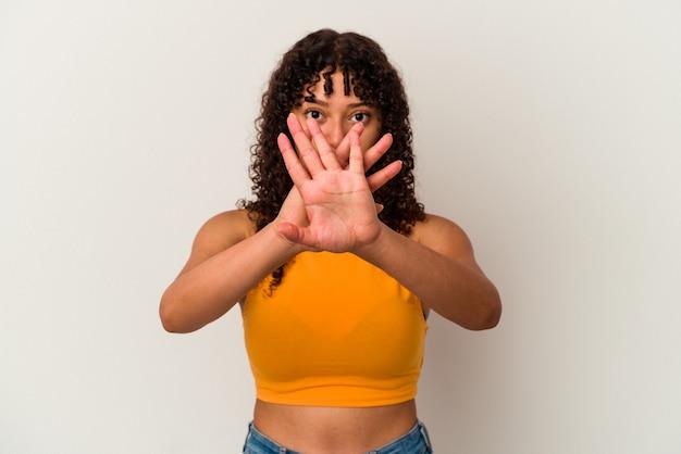 Junge gemischte rassenfrau lokalisiert auf weißer wand, die eine verweigerungsgeste tut