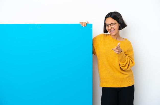 Junge gemischte rassenfrau mit einem großen blauen plakat lokalisiert auf weißem hintergrund, der nach vorne zeigt und lächelt