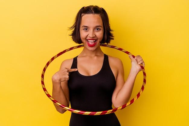 Junge gemischte rassengymnastikfrau lokalisiert auf gelbe wandperson, die von hand auf einen hemdkopierraum zeigt, stolz und zuversichtlich