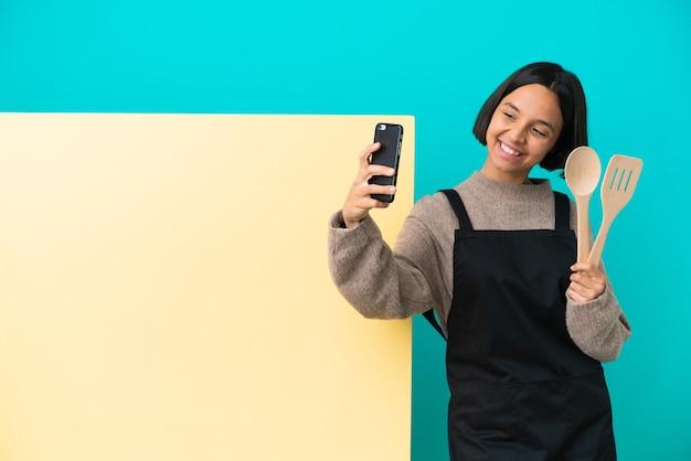 Junge gemischte rassenkochfrau mit einem großen plakat lokalisiert auf blauem hintergrund, der ein selfie macht
