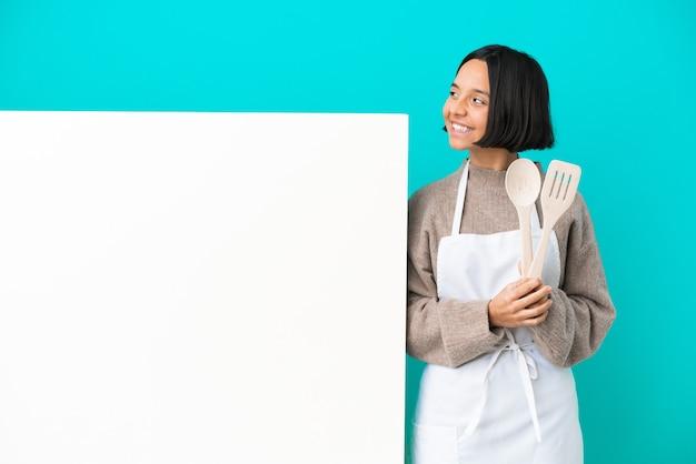 Junge gemischte rassenkochfrau mit einem großen plakat lokalisiert auf blauem hintergrund glücklich und lächelnd