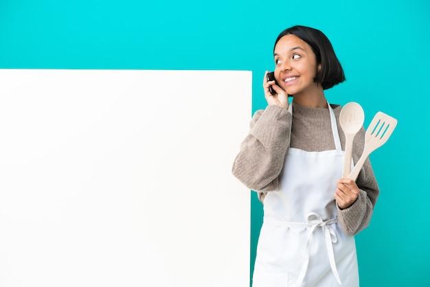 Junge gemischte rassenkochfrau mit einem großen plakat lokalisiert auf blauer wand, die ein gespräch mit dem mobiltelefon mit jemandem hält