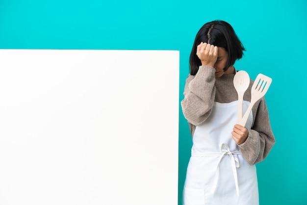 Junge gemischte rassenkochfrau mit einem großen plakat lokalisiert auf blauer wand mit kopfschmerzen