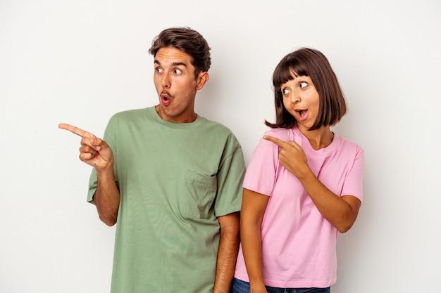 Junge gemischte rassenpaare, die auf weißem hintergrund isoliert sind, zeigen mit dem daumenfinger weg, lachen und sorglos.
