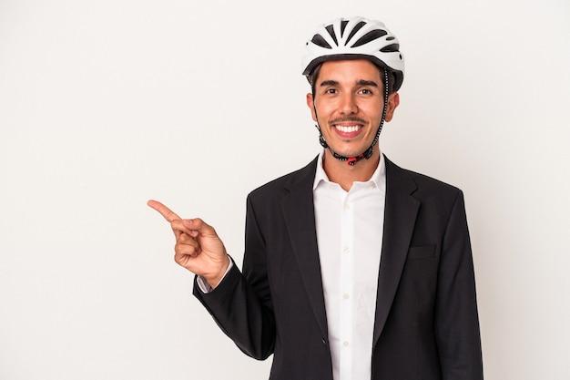 Junge gemischte rennen geschäftsmann trägt einen fahrradhelm isoliert auf weißem hintergrund lächelnd und beiseite zeigend, etwas an der leerstelle zeigend.