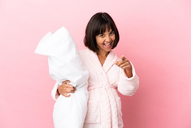 Junge gemischte schwangere frau isoliert auf rosa hintergrund im pyjama und zeigt mit einem selbstbewussten ausdruck mit dem finger auf sie