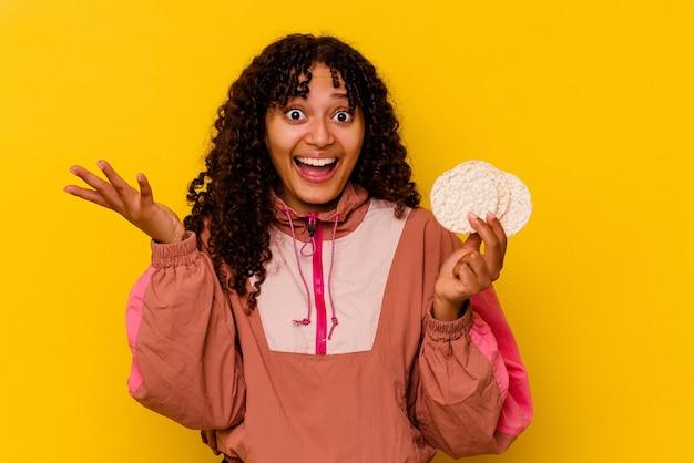 Junge gemischte sportfrau, die einen reiskuchen auf gelbem hintergrund hält, der eine angenehme überraschung empfängt, aufgeregt und die hände hebt.