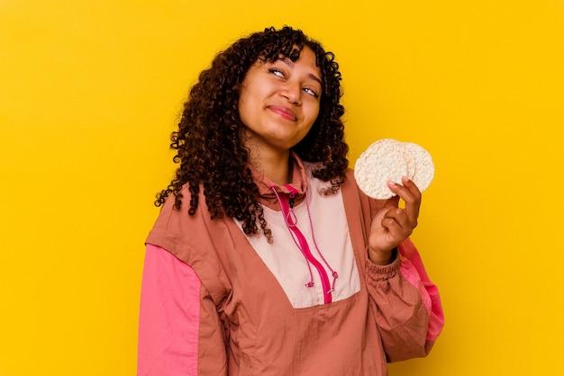 Junge gemischte sportfrau, die einen reiskuchen auf gelbem hintergrund hält und davon träumt, ziele und zwecke zu erreichen