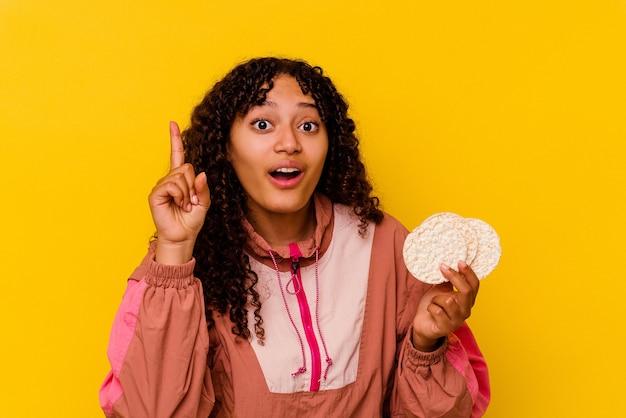 Junge gemischte sportfrau mit reiskuchen auf gelbem hintergrund mit einer idee, inspirationskonzept.