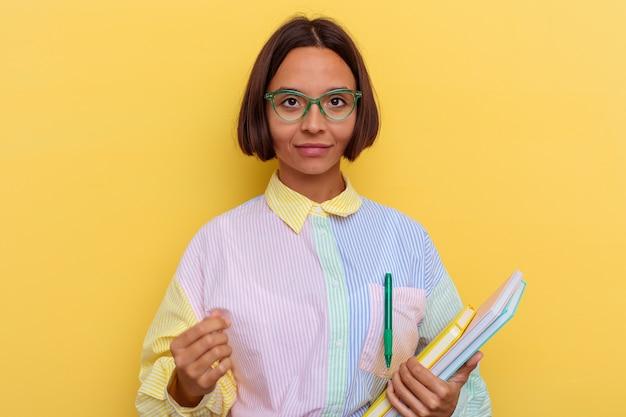 Junge gemischte studentenfrau, die auf gelbem hintergrund isoliert ist, sagt eine geheime heiße bremsnachricht und schaut beiseite