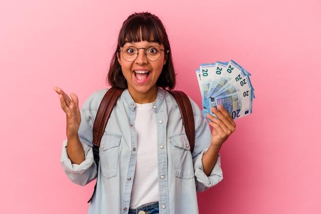Junge gemischte studentenfrau, die rechnungen einzeln auf rosafarbenem hintergrund hält, die eine angenehme überraschung erhalten, aufgeregt und die hände heben.