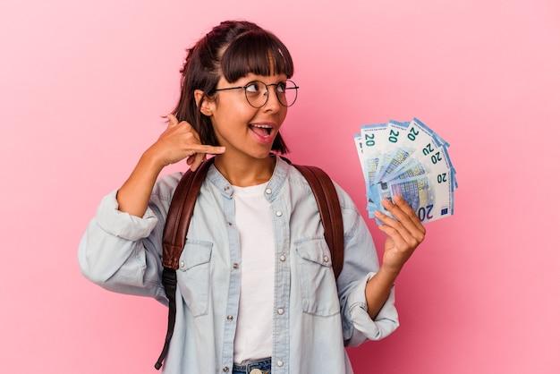 Junge gemischte studentenfrau, die rechnungen einzeln auf rosafarbenem hintergrund hält, die eine handyanrufgeste mit den fingern zeigen.