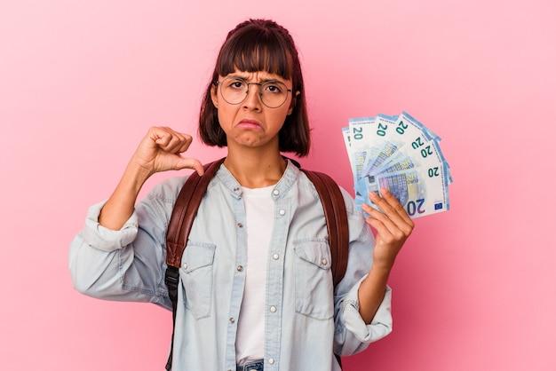 Junge gemischte studentenfrau, die rechnungen einzeln auf rosafarbenem hintergrund hält, fühlt sich stolz und selbstbewusst, beispiel zu folgen.